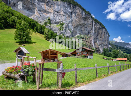 View of a farm house near Lauterbrunnen and with Staubbach Falls in the background, Interlaken-Oberhasli, Bern, Switzerland - Stock Photo