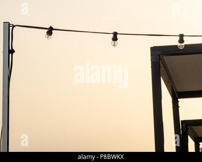String of outdoor party lights on rooftop pole, Barcelona, Spain. - Stock Photo