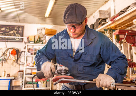 A young man welder in a blue T-shirt, goggles and construction gloves processes metal an angle grinder in the garage, in the background a lot of tools - Stock Photo
