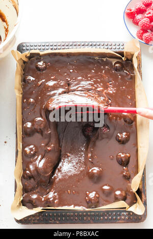 Spreading chocolate brownies batter cake with raspberries on baking tray - Stock Photo