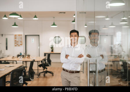 Smiling Asian businessman leaning against a glass wall at work - Stock Photo