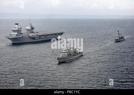 HMS QUEEN ELIZABETH (RO8) aircraft carrier at sea on 28 June 2017 accompanied by  Type 23 frigatesHMS Sutherland (front) and HMS Iron Duke. Courtesy UK Ministry of Defence photo 45162784 - Stock Photo