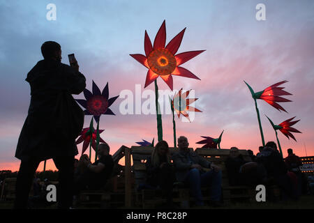 Hoppegarten, Germany, woman takes a photo of bright artificial flowers in the evening at Lollapalooza Berlin 2017 at the Hoppegarten racecourse - Stock Photo