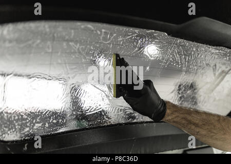 Car tinting - Worker applying tinting foil on car window. - Stock Photo