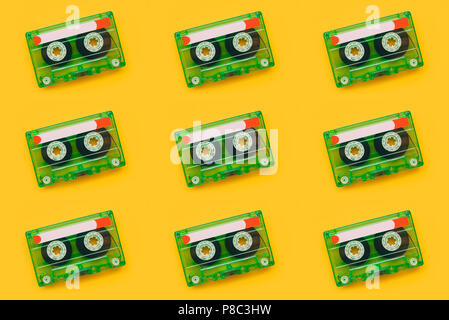 Seamless pattern background of audio cassettes on bright yellow backdrop, minimalistic retro style top view composition - Stock Photo