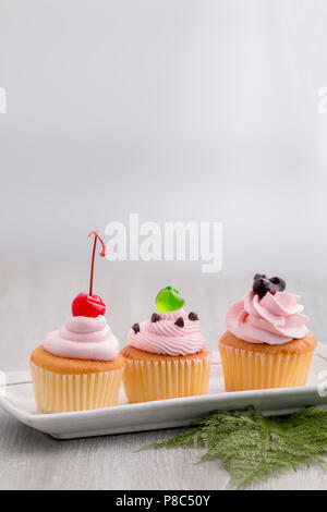 Pink cupcake with red cherry,blueberry sauces,green jelly and chocolates on wood.Copy space. - Stock Photo