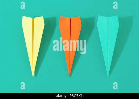 Flat lay set colorful paper plane on pastel turquoise background. Top view creative travel background concept - Stock Photo