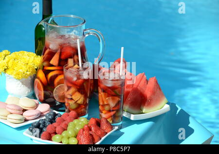 Pool party with sangria pitcher, fruit cocktails and refreshments by the swimming pool. Summer lifestyle, topical vacation, fun and relaxation theme. - Stock Photo