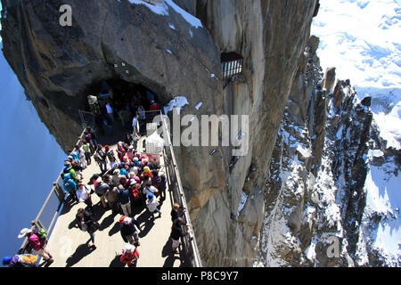 Tourists at the observation platform on top of Aiguille-du-Midi in the Mont Blanc massif in France - Stock Photo