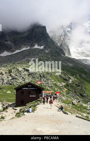 Hikers at a  mountain hut at the Plan-de-l'Aiguille in the Mont Blanc massif in France - Stock Photo