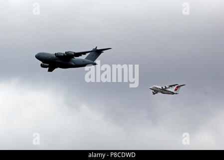 A C17  Globemaster and a BAe 146 fly in formation over the QE2 Olympic Park, as par of the RAF Centennial Celebrations - Stock Photo