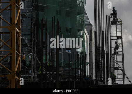 Manila, Philippines. 10th July, 2018. Filipino construction workers stand on top of a scaffoldings at a building site in Manila, Philippines on Tuesday. July 10, 2018. Philippines President Rodrigo Duterte is set to have his third State of the Nation Address (SONA) on July 23 where he will highlight his achievements since taking office, such as infastructure and economic development projects. Credit: Basilio H. Sepe/ZUMA Wire/Alamy Live News - Stock Photo