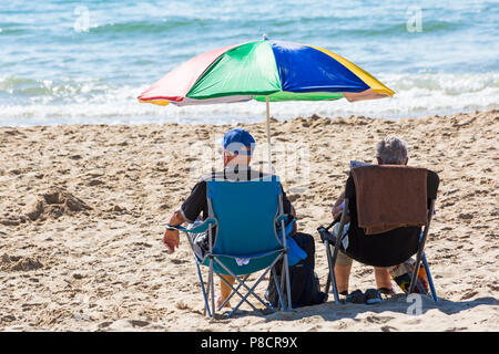 Bournemouth, Dorset, UK. 11th July 2018. UK weather: another hot sunny day in Bournemouth with no sign of the heatwave ending yet, as sunseekers head to the seaside at Bournemouth beaches. Couple sitting in chairs under colourful parasol enjoying the sunshine. Credit: Carolyn Jenkins/Alamy Live News - Stock Photo