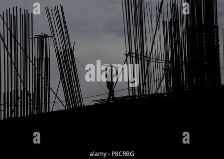 Manila, Philippines. 10th July, 2018. A construction worker carries a piece of scaffolding at a building site in Manila, Philippines on Tuesday. July 10, 2018. Philippines President Rodrigo Duterte is set to have his third State of the Nation Address (SONA) on July 23 where he will highlight his achievements since taking office, such as infastructure and economic development projects. Credit: Basilio H. Sepe/ZUMA Wire/Alamy Live News - Stock Photo