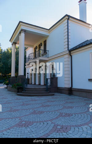 Entrance to a two-storey building with white columns and high windows. Around on the ground a tile with a floral pattern . For your design - Stock Photo