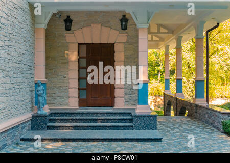 The main entrance to the building with columns and decorative stone sculptures . For your design - Stock Photo
