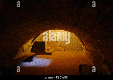 The room with a ceiling in the form of an arch with benches made of two wooden blocks and one board under a wall lined with stone. . For your design - Stock Photo