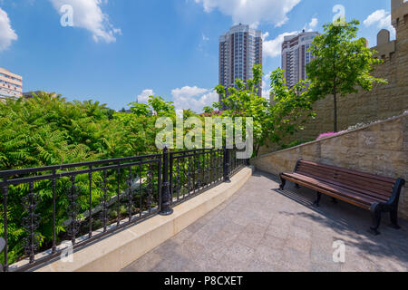A bench for rest standing on a viewing platform in a cozy place near the tops of green trees with a beautiful view of the city houses against the back - Stock Photo