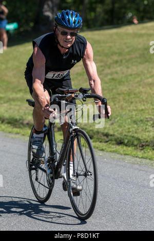 Male competitor in the bike segment in the 2018 Stissing Triathlon - Stock Photo