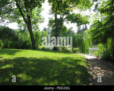 The lawn is in the shade, with a thick green grass around which the path goes. Behind the trees is a pond... . For your design - Stock Photo
