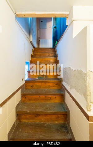 A narrow staircase in the room leading up with wooden stairs . For your design - Stock Photo
