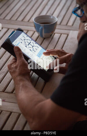 A senior man working on the New York Times crossword online on an iPad - Stock Photo