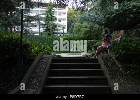 A woman sitting alone on a bench. Perhaps he is waiting for his chosen one . For your design - Stock Photo