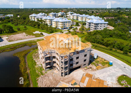 Aerial view of Condominium new home construction showing wood trusses atop on a cement block of 9 individual home units - Stock Photo