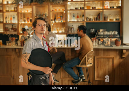 Waiter standing in a trendy bar ready to serve customers - Stock Photo