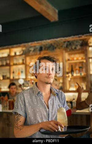 Young waiter serving cocktails in a trendy bar - Stock Photo