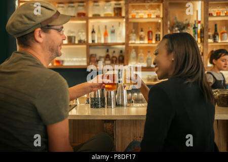 Two smiling friends sitting in a bar cheering with drinks - Stock Photo