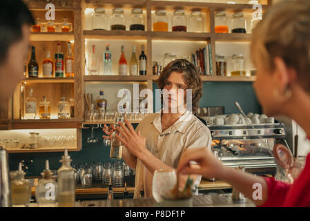 Bartender taking drink orders from customers in a trendy bar - Stock Photo