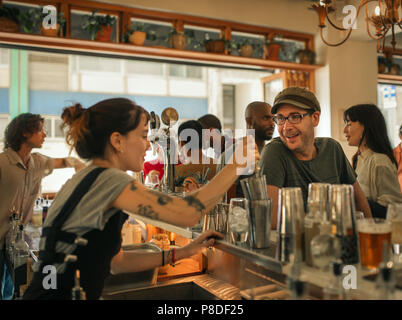 Smiling patron ordering drinks in a trendy bar - Stock Photo