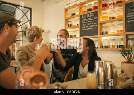 Smiling friends cheering with drinks in a trendy bar - Stock Photo
