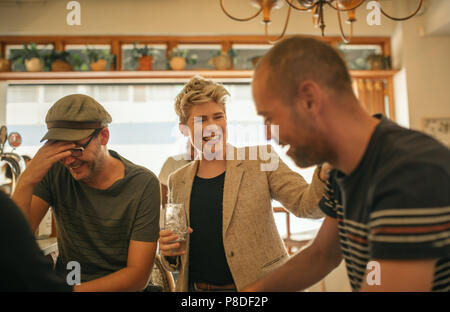 Friends laughing and having drinks together in a bar - Stock Photo