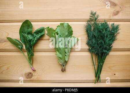 Spinach, green salad and dill on a wooden surface. Mix of greens. Healthy foods. - Stock Photo