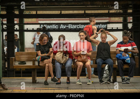 Independence Day subway riders wait for a train at the Atlantic Avenue-Barclays Center station in Downtown Brooklyn in the New York subway on Wednesday, July 4, 2018. (© Richard B. Levine) - Stock Photo