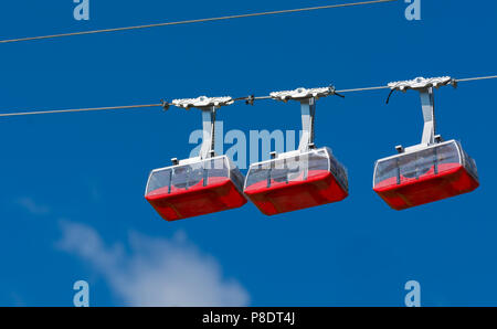 Three red toy cableways on their rope. Sky in the background - Stock Photo