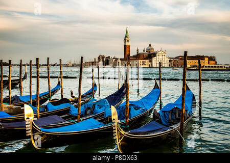 Gondolas docked in Venice, Italy in the morning.  In the background is the island of San Giorgio Maggiore - Stock Photo