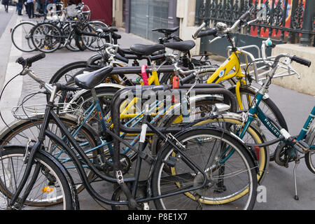 Bicycles parked on the street in Paris, France. - Stock Photo