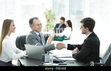 handshake business people behind a Desk in the office - Stock Photo