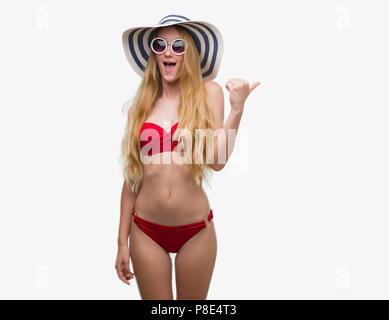 Blonde teenager woman wearing bikini, sunglasses and summer hat pointing and showing with thumb up to the side with happy face smiling - Stock Photo