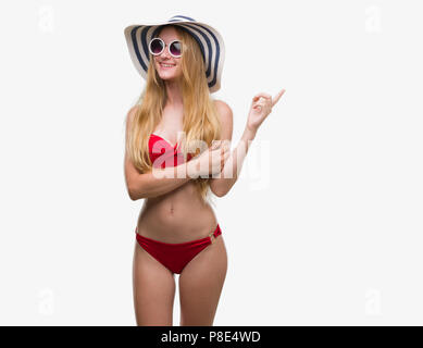 Blonde teenager woman wearing bikini, sunglasses and summer hat very happy pointing with hand and finger to the side - Stock Photo