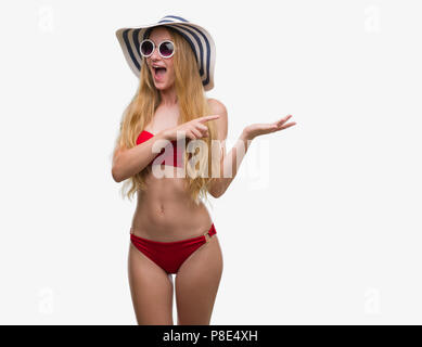 Blonde teenager woman wearing bikini, sunglasses and summer hat very happy pointing with hand and finger - Stock Photo
