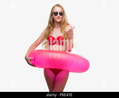 Blonde teenager woman wearing bikini and holding pink floater pointing and showing with thumb up to the side with happy face smiling - Stock Photo