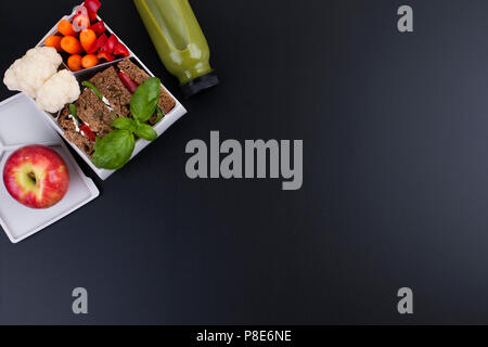 School lunch in a plastic container. Juice from fresh berries and toast with vegetables for a healthy lunch. Black background and free space for text. Lunch at the office. Copy space - Stock Photo