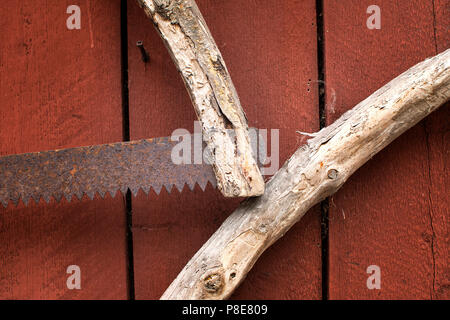 Closeup of an old handmade saw with a wooden handle and rusty blade. - Stock Photo