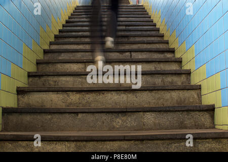 Legs in motion blur running up stairs in subway station. - Stock Photo