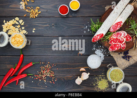 Slices of chopped sausage, spices in jars and scattered, pepper chili and tomatoes on a dark wooden rustic background. - Stock Photo