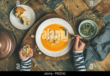 Fall warming pumpkin cream soup with seeds and bread croutons - Stock Photo